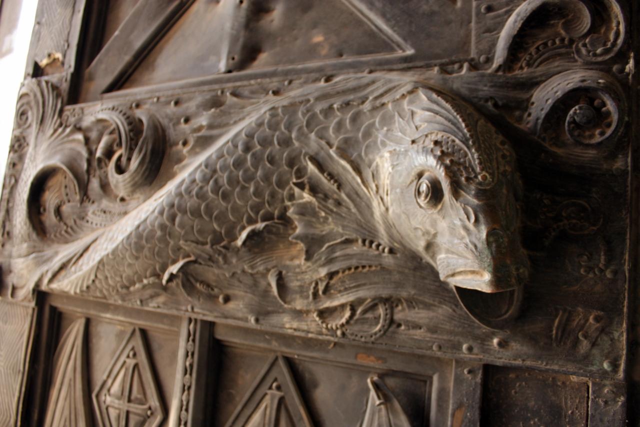 Скульптурное изображение рыбы,на дверях собора.