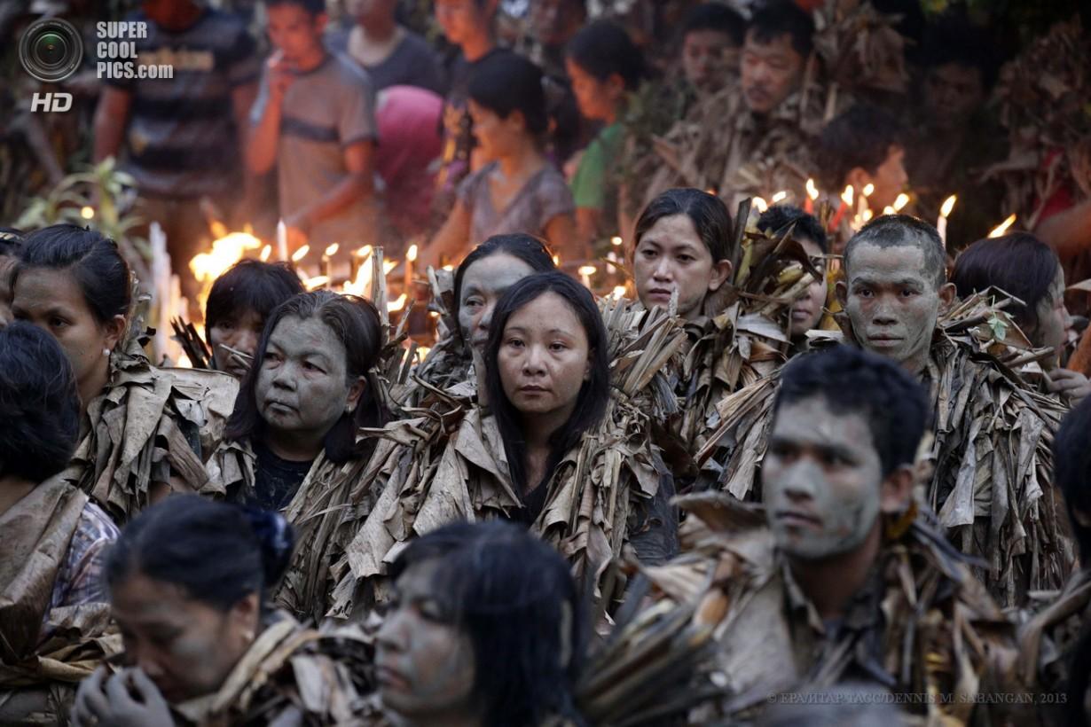 Филиппины. Алиага, Нуэва-Эсиха. 24 июня. Филиппинские католики, покрытые грязью и одетые в сухие