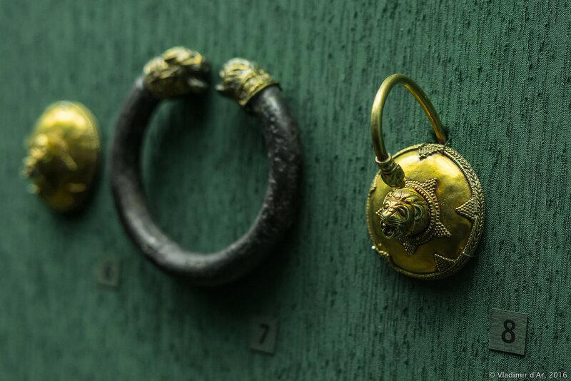 Височное кольцо со скульптурным изображением головы льва в центре и загнутой вперед дужкой с изображением головы барана.