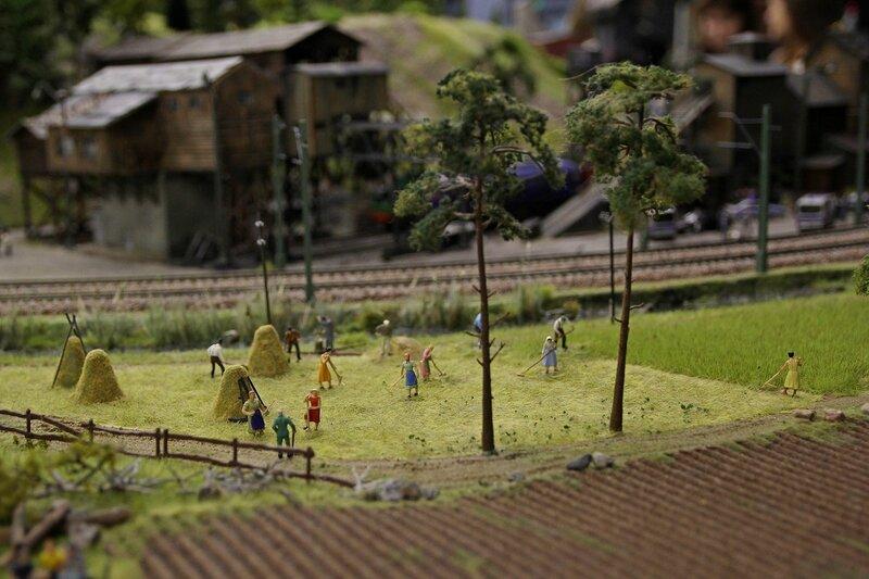 Гранд макет: заготовка сена. Двое человек косят траву, остальные граблями собирают высохшее сено в стога.