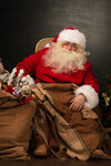 Santa Claus with a huge bag full of Christmas presents sitting in a comfortable chair near the Christmas tree at home