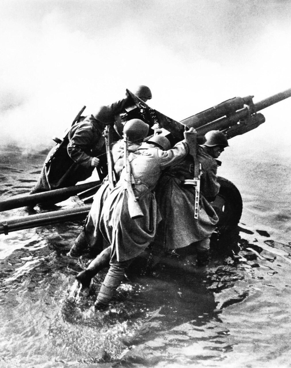 Советские артиллеристы транспортируют 76-мм дивизионную пушку ЗиС-3 во время форсирования Одера. Германия. Декабрь 1944
