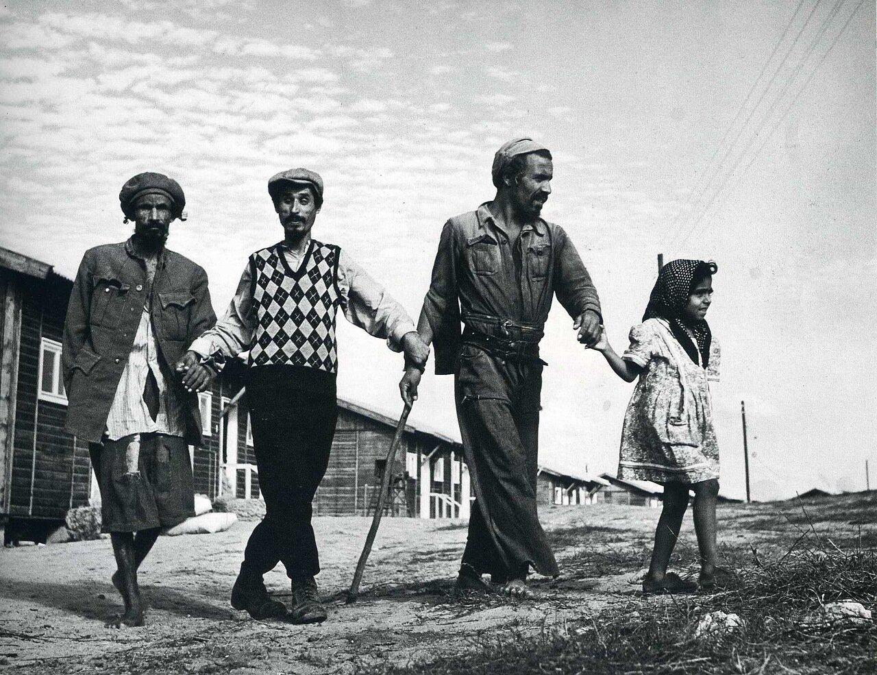 1950. Галилея, недалеко от Гедеры. Деревня слепых иммигрантов, страдающих трахомой. Трое мужчин идут в столовую