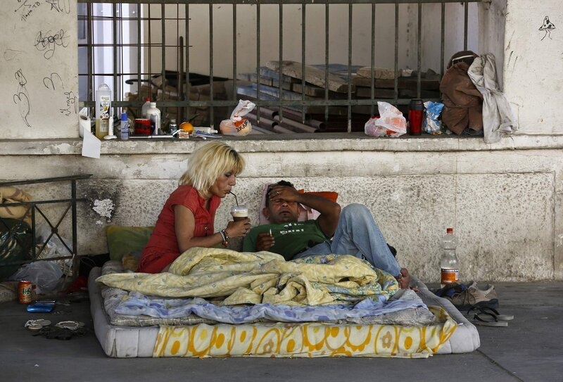 Marialena, a homeless AIDS sufferer and former drug addict who is on a methadone rehabilitation program, drinks coffee next to her boyfriend Dimitrios in central Athens
