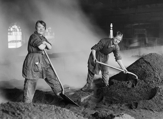 War workers feed the charcoal kilns used for purifying sugar at a sugar ref