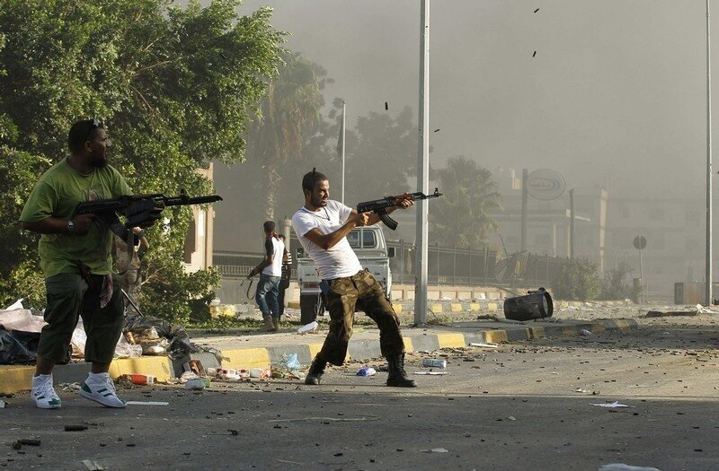 Libyan rebel fighter fire their weapons during a fight for the final push to flush out Muammar Gaddafi's forces in Abu Salim district in Tripoli