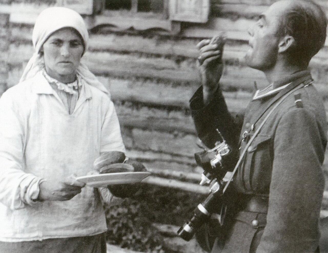 1941. Белоруссия, немецкий репортер  ест огурец, предложенный крестьянкой