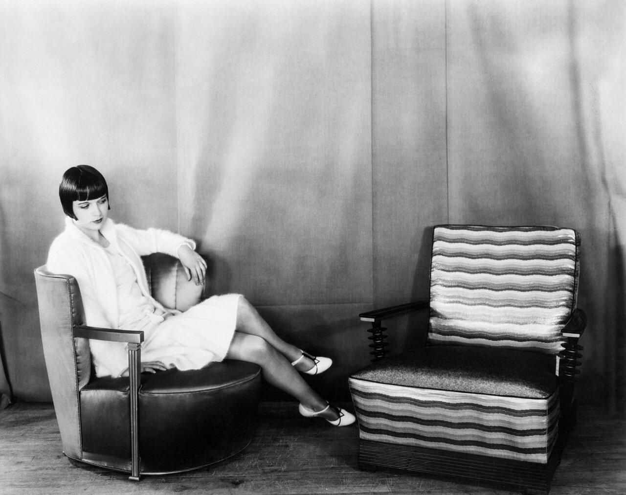 5/25/28: Miss Louise Brooks, movie star, is shown studying the fascinating lines of the modern chair.