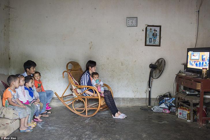 16-летняя Сяо Синь смотрит мультфильмы со своей годовалой дочерью в деревне Гуандон. Она начала встр