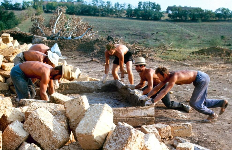 Сельские мальчики купаются в резервуарах с водой для замеса раствора, пока студенты трудятся не покл