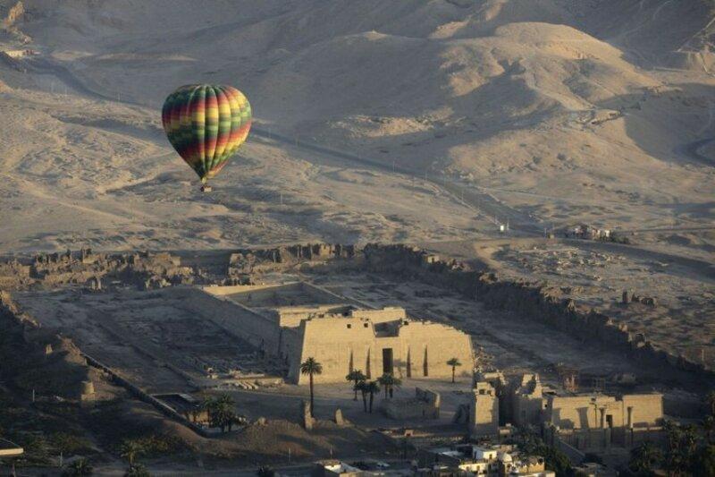 Воздушный шар летит над храмом Рамзеса III в Мединет Хабу на западном берегу реки Нил в Луксоре, Египет