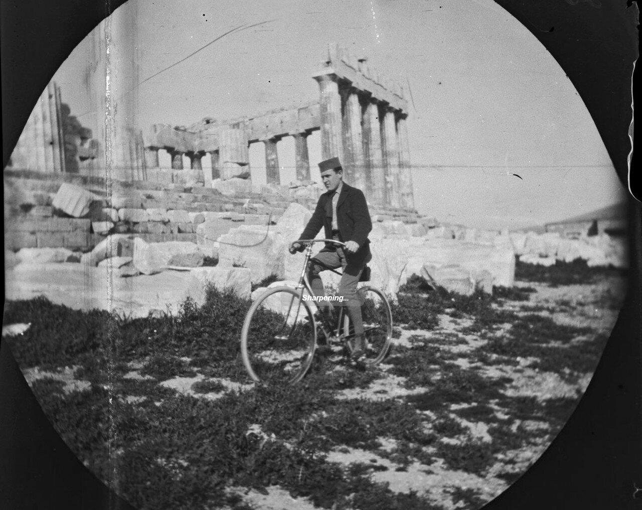 Том Аллен ездит на велосипеде по Акрополю. Позади него Парфенон