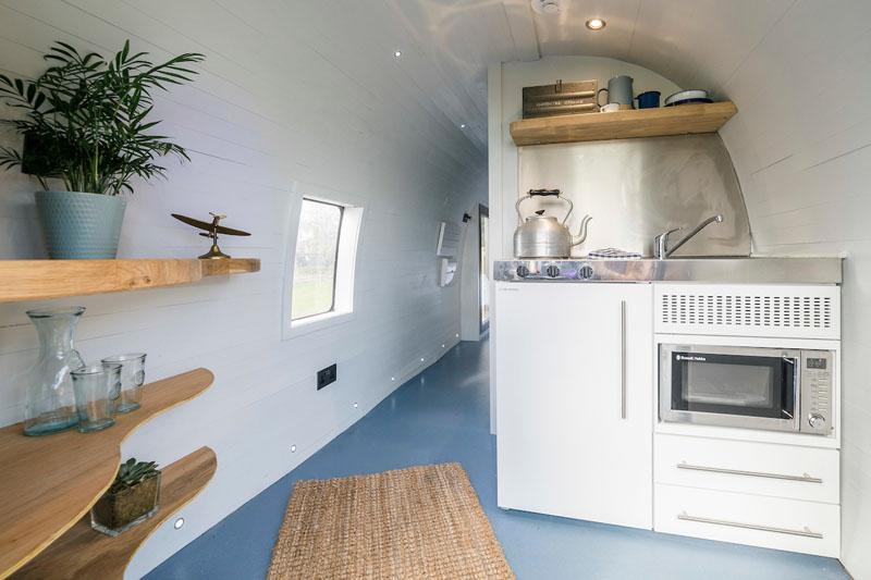 В помещении, выполненном в светлых тонах, есть мини-кухня со стойкой из нержавеющей стали. Деревянны