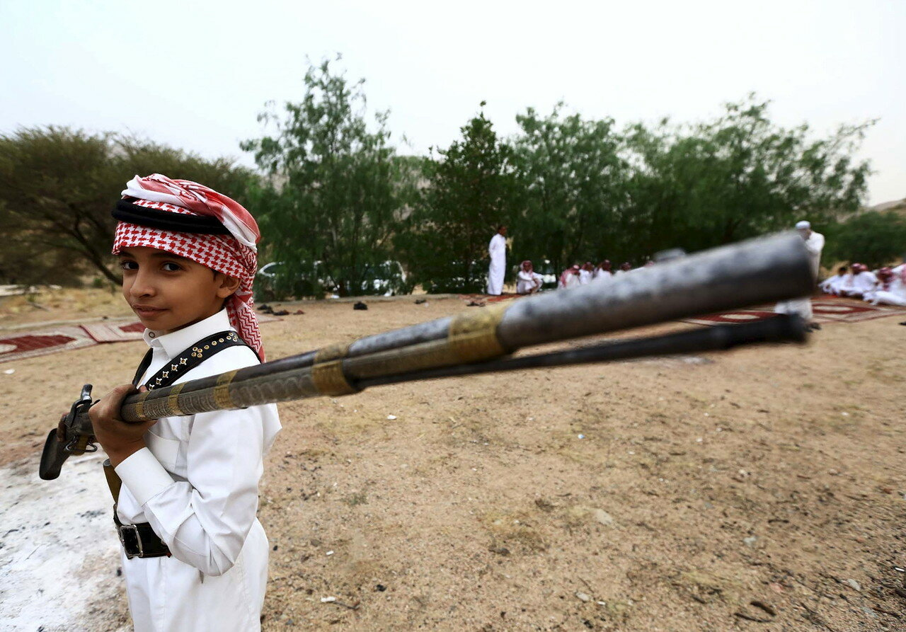 Boy holds a weapon as he poses for a photo during a traditional excursion near the western Saudi city of Taif