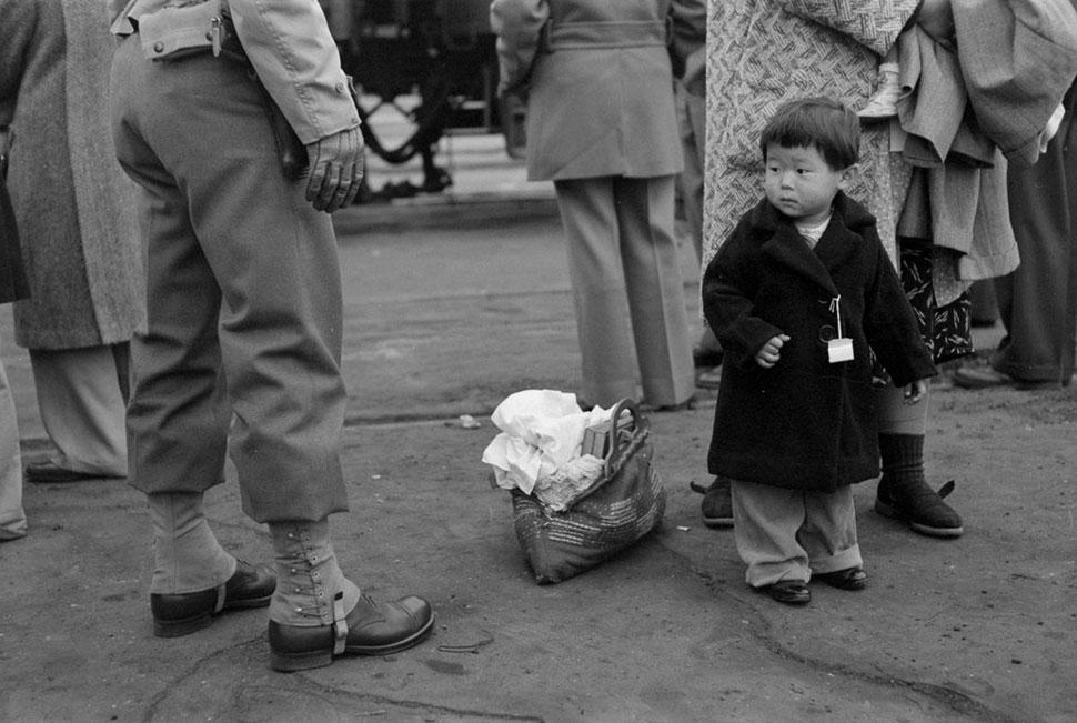 Ребенок смотрит на солдата, который собирает вещи его семьи для принудительной эвакуации.