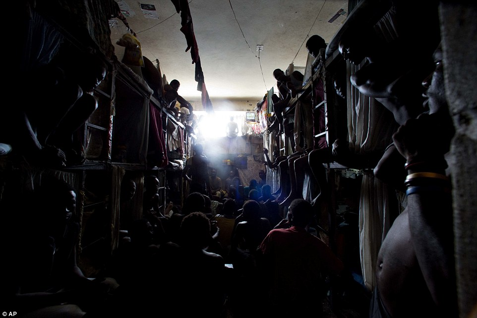 Заключенные смотрят телевизор в переполненной камере.