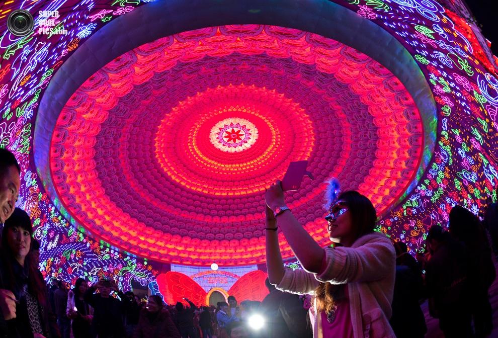 Девушка фотографирует инсталляцииво время Цзыгунского международного фестиваля фонарей,Цзыгун,