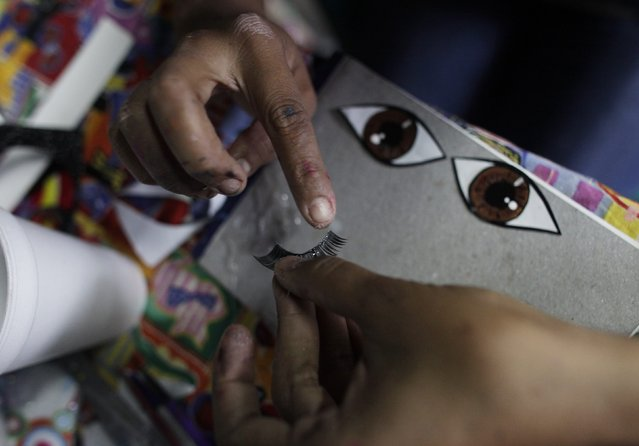 Adriana Ramirez puts glue on fake eyelashes to be used for a pinata depicting TV celebrity Kim Karda