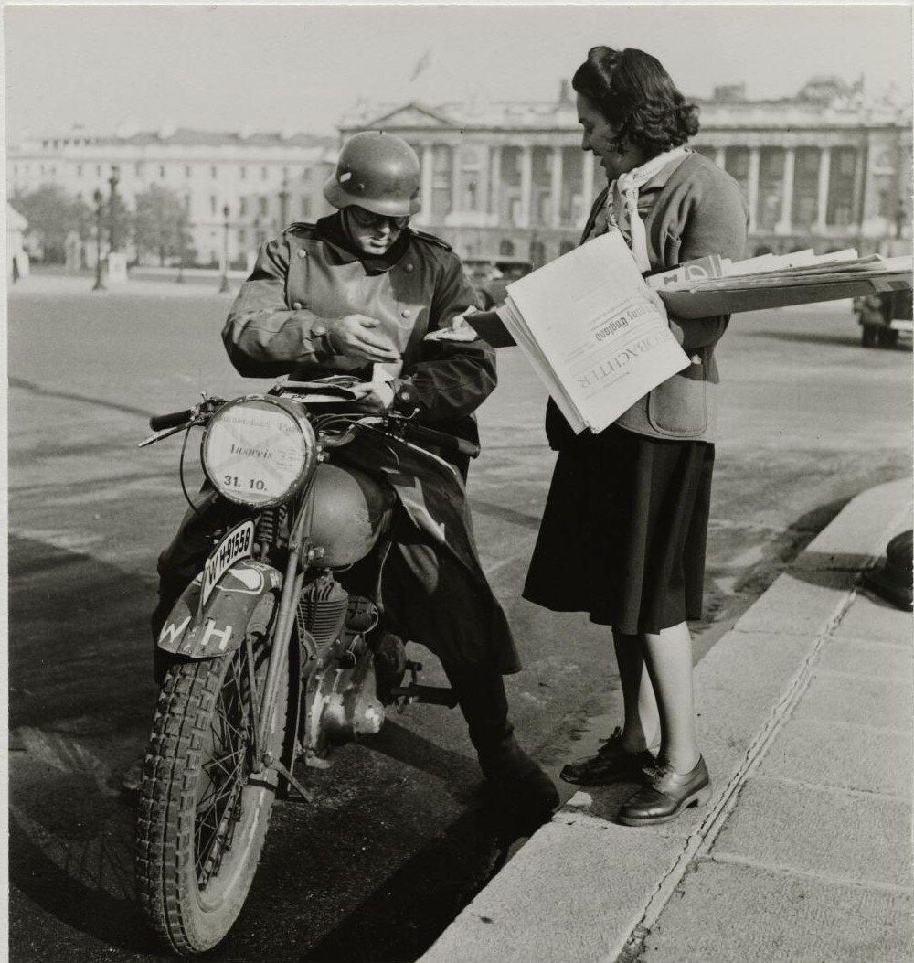 Немецкий солдат на своем мотоцикле покупает газету на площади Согласия