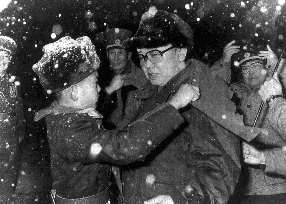 12. Мальчик надевает шарф на лидера Северной Кореи Ким Чен Ира в овремя визита в военную школу в Пхе