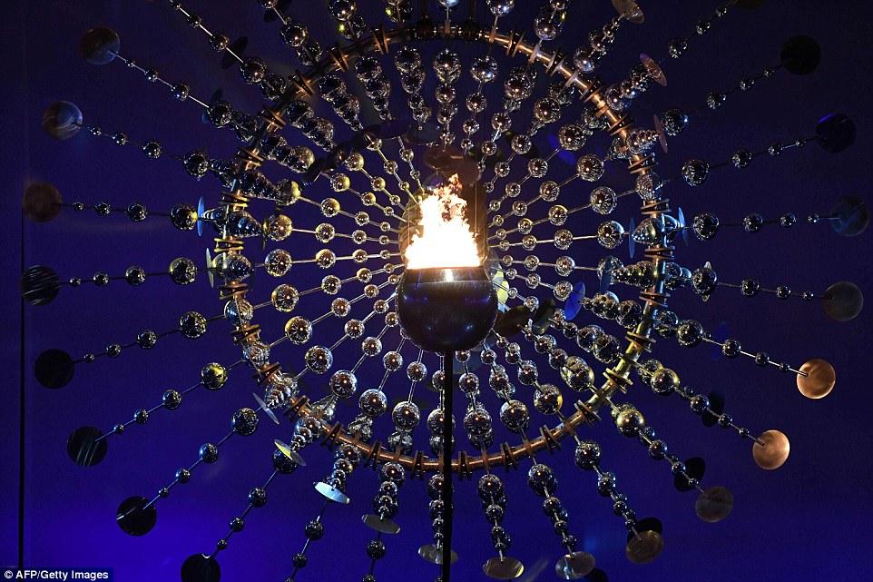 Котел с олимпийским огнем ярко горит во время церемонии открытия.