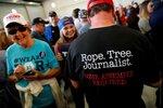 Мужчина в футболке с надписью «Веревка. Дерево. Журналист» идет среди сторонников Д