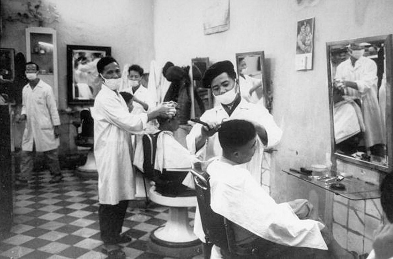 Парикмахеры в марлевых повязках подстригают клиентов
