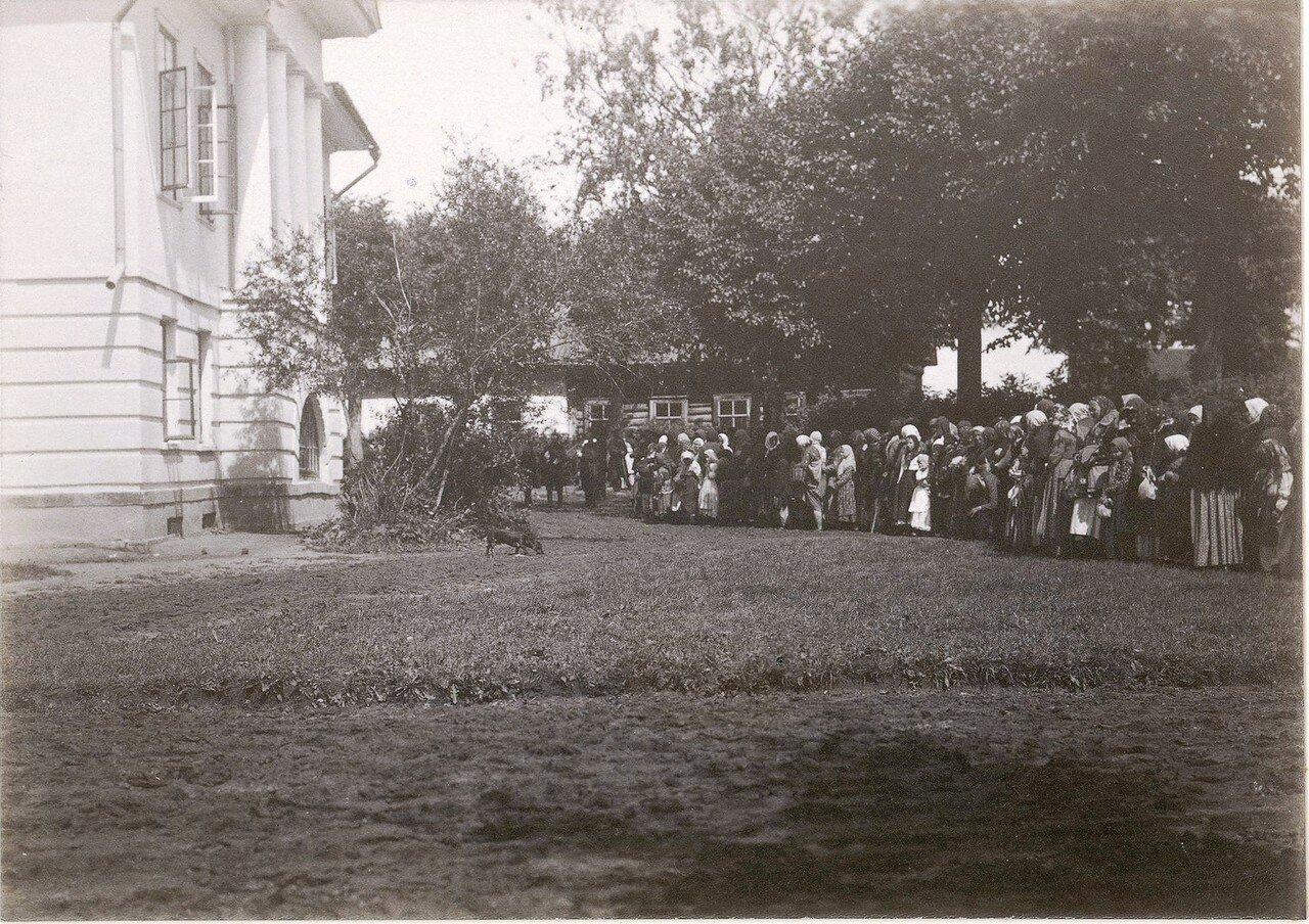 Крестьяне у Конторского флигеля в день праздника. У женщин в руках узелки с подношениями господам.1880-е.