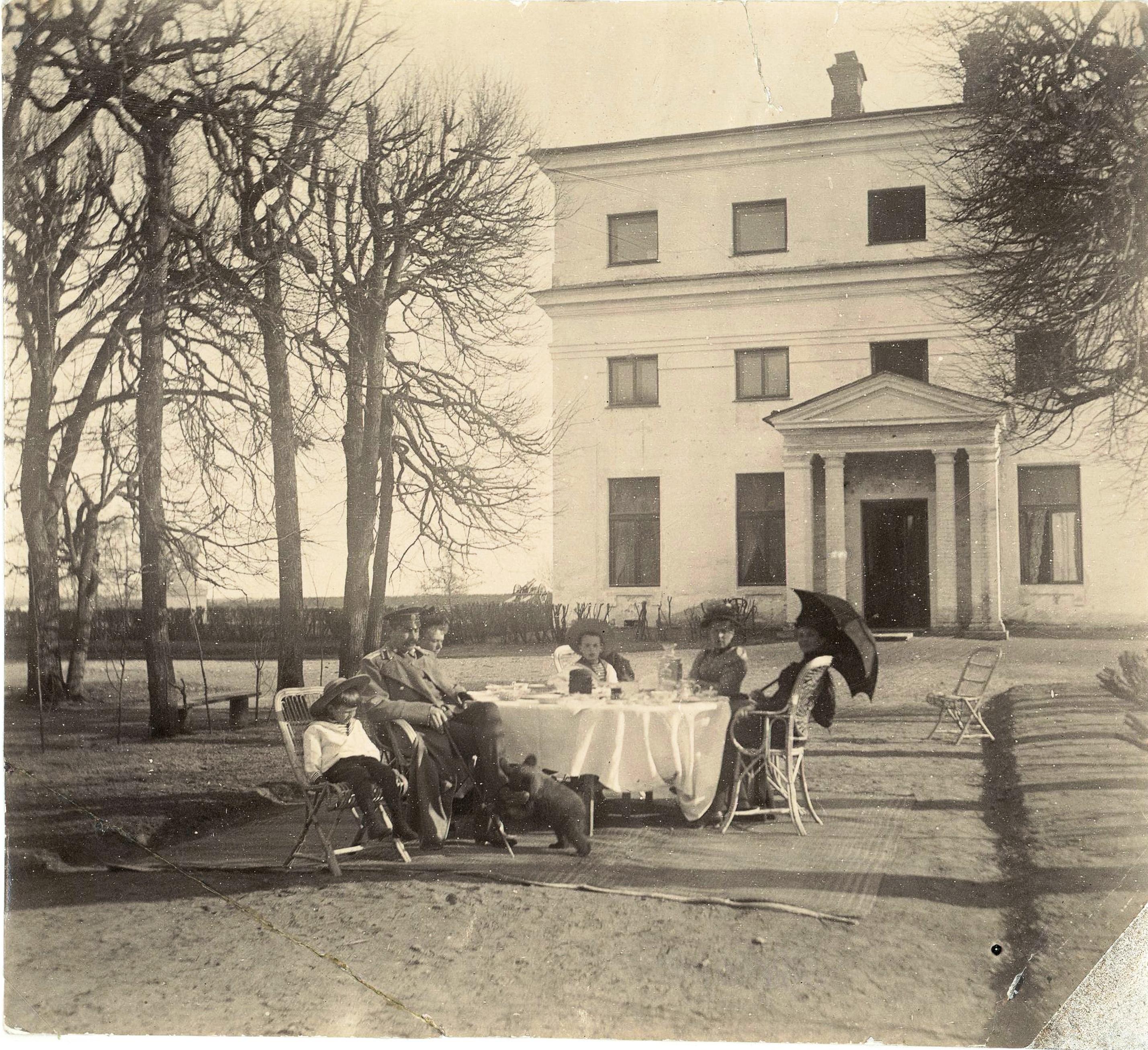 У западного оранжерейного флигеля семья князей Юсуповых за столом с гостями. 1892