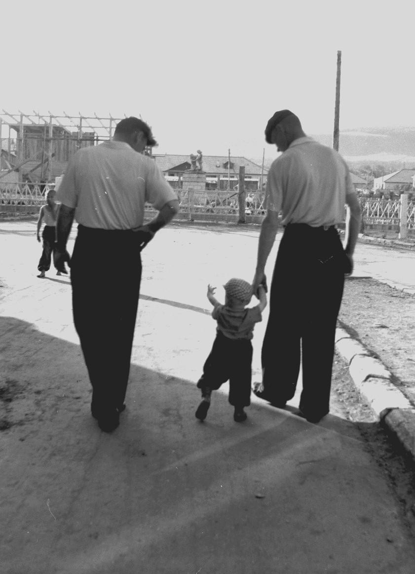Двое мужчин с малышом возле строительной площадки