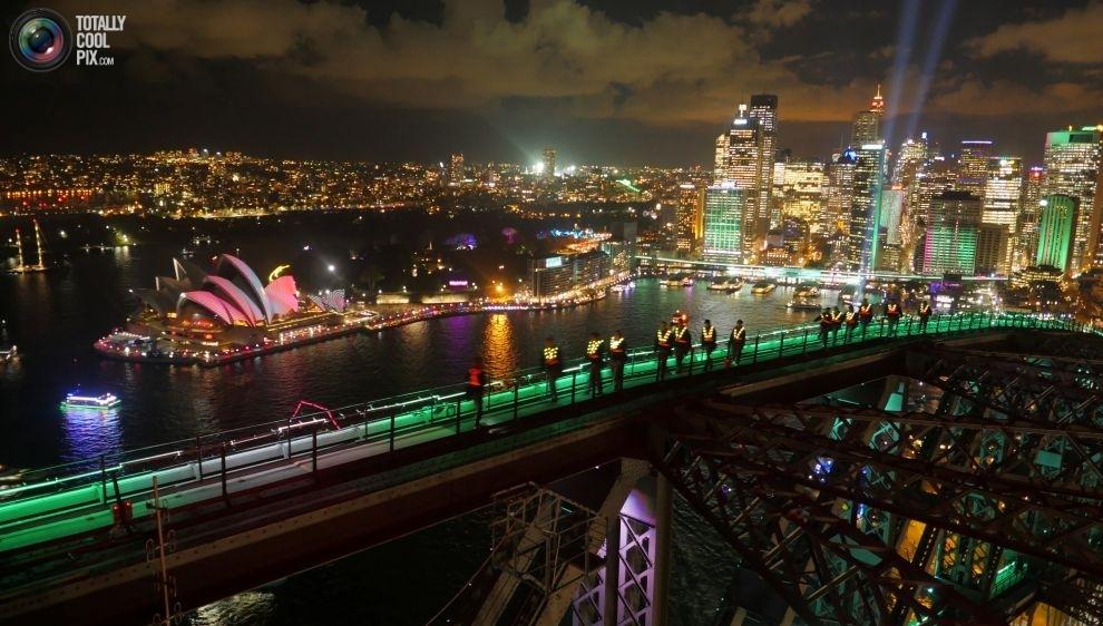 Люди любуются Сиднейским оперным театром с моста Харбор-Бридж в день открытия фестиваля Vivid Sydney
