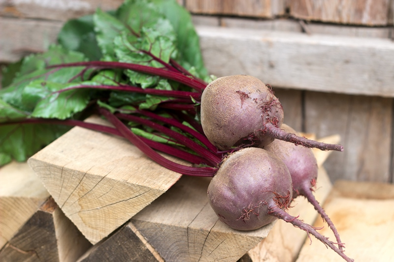 Beetroot with leaves on a wooden background. Rustic style, selective focus.