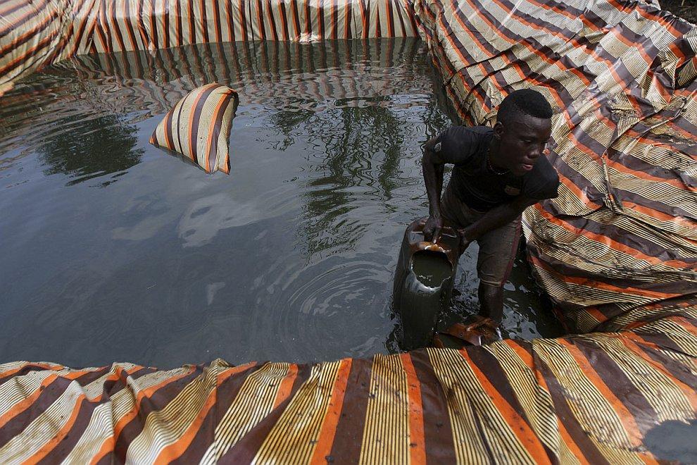 Старый знакомый, 48-летний «предприниматель». Черпает сырую нефть с земли ведрами. (Фото Akin