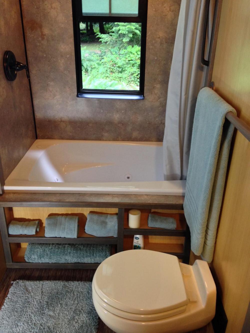 Возле кухни— санузел сдушем иполноценной ванной-джакузи (она уходит встенную нишу справа).