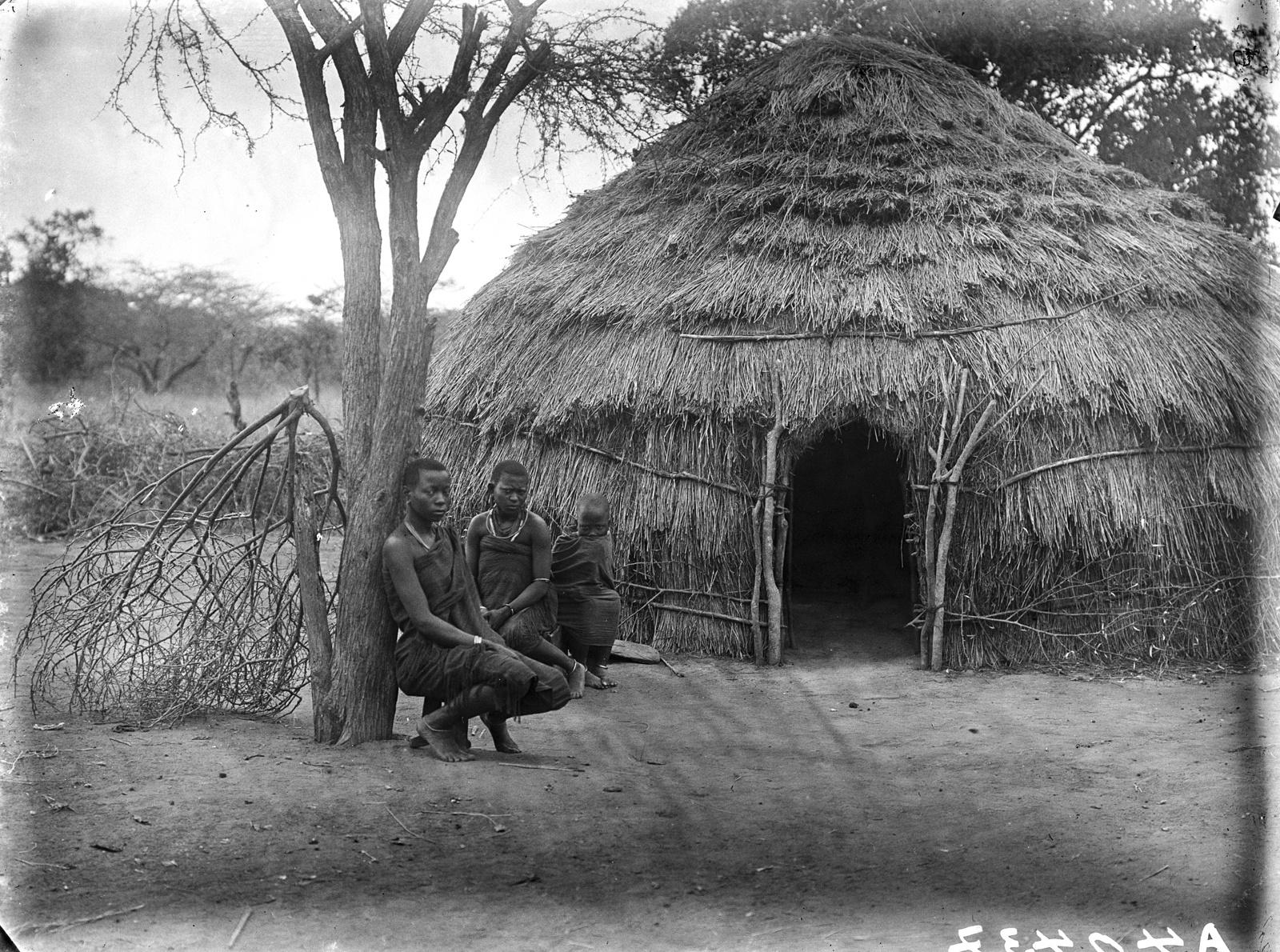148. Две женщины и ребенок народности камба перед круглой соломенной хижиной