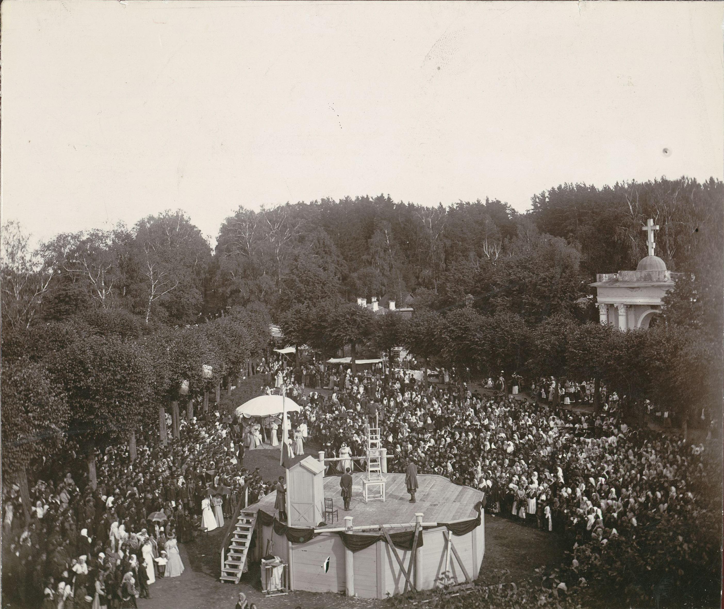 Народное гулянье в парке. Цирковое представление на подмостках. Под большим белым зонтом семья князей Юсуповых.1890-е