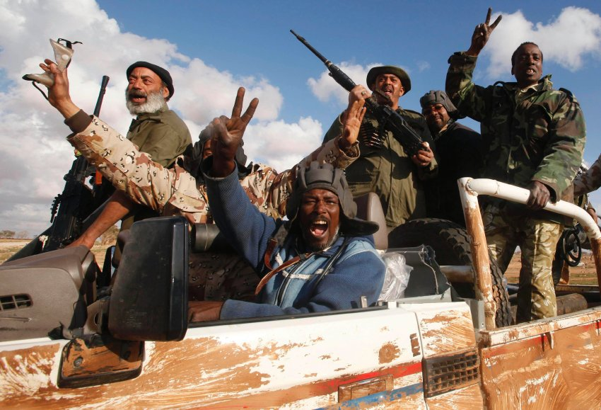 Rebels celebrate in a vehicle along the road between Benghazi and Ajdabiyah