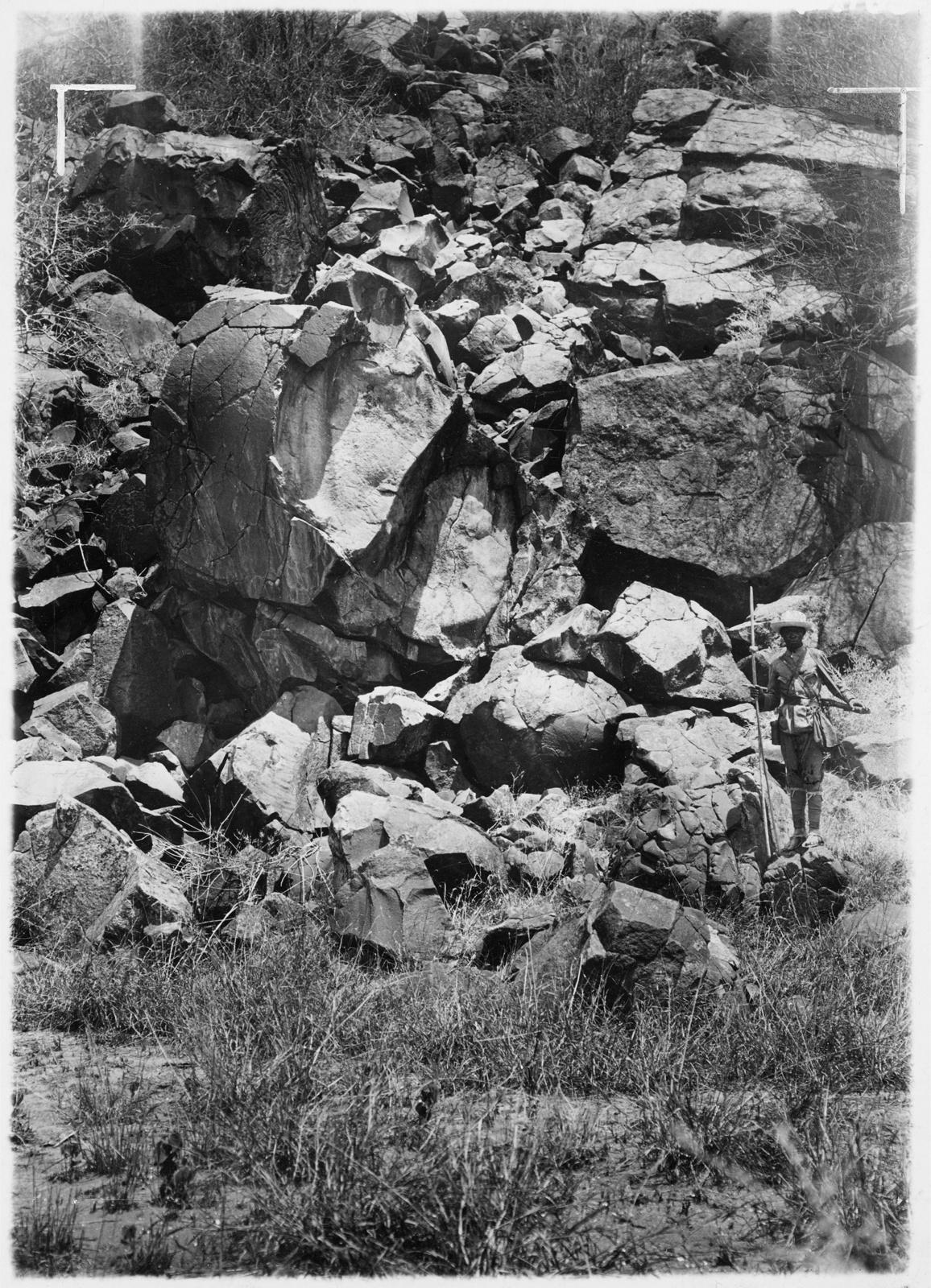 17. Человек перед крутым склоном с рухнувшими лавовыми камнями