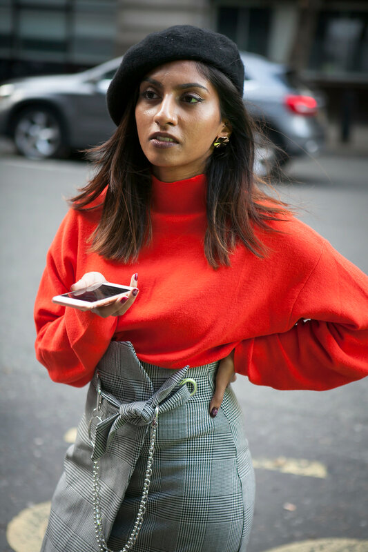 LONDON, ENGLAND - September 15, 2017 Beautiful and stylish woman in red blouse and skirt posing during the London Fashion Week. outside Eudon Choi