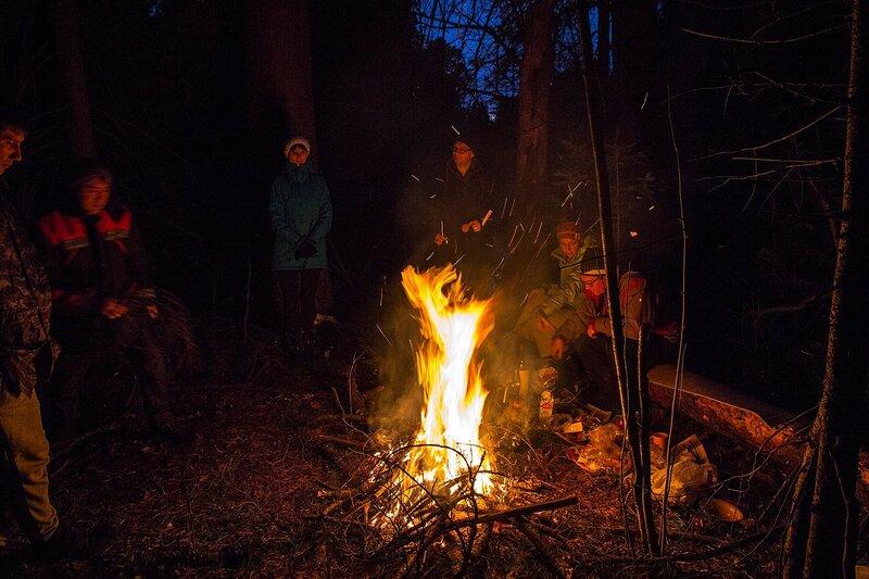 У ночного костра: яркий костёр с искрами в ночном лесу, путешественники сидят на бревне вокруг него