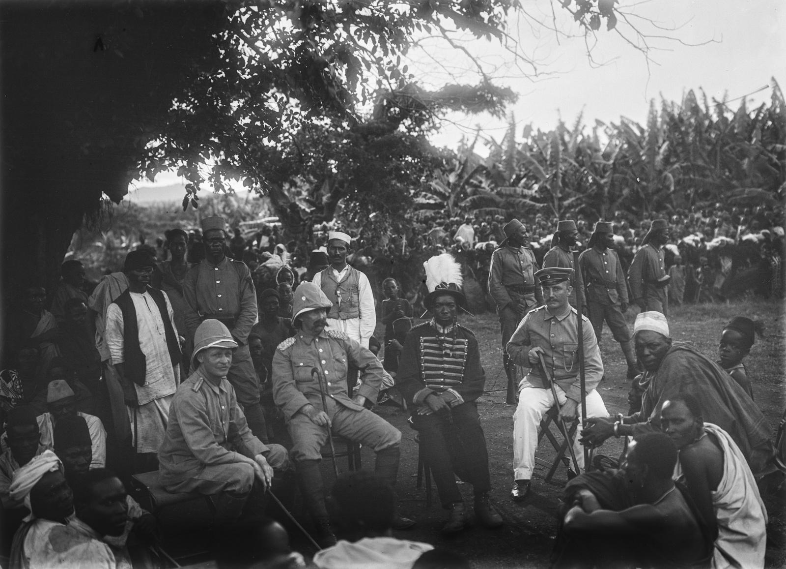 74. Встреча в Марангу. На стульях сидят (слева направо) граф Ганс Германн фон Швайниц, вождь племени чагга в военной форме, капитан Курт Йоханнес и другие люди