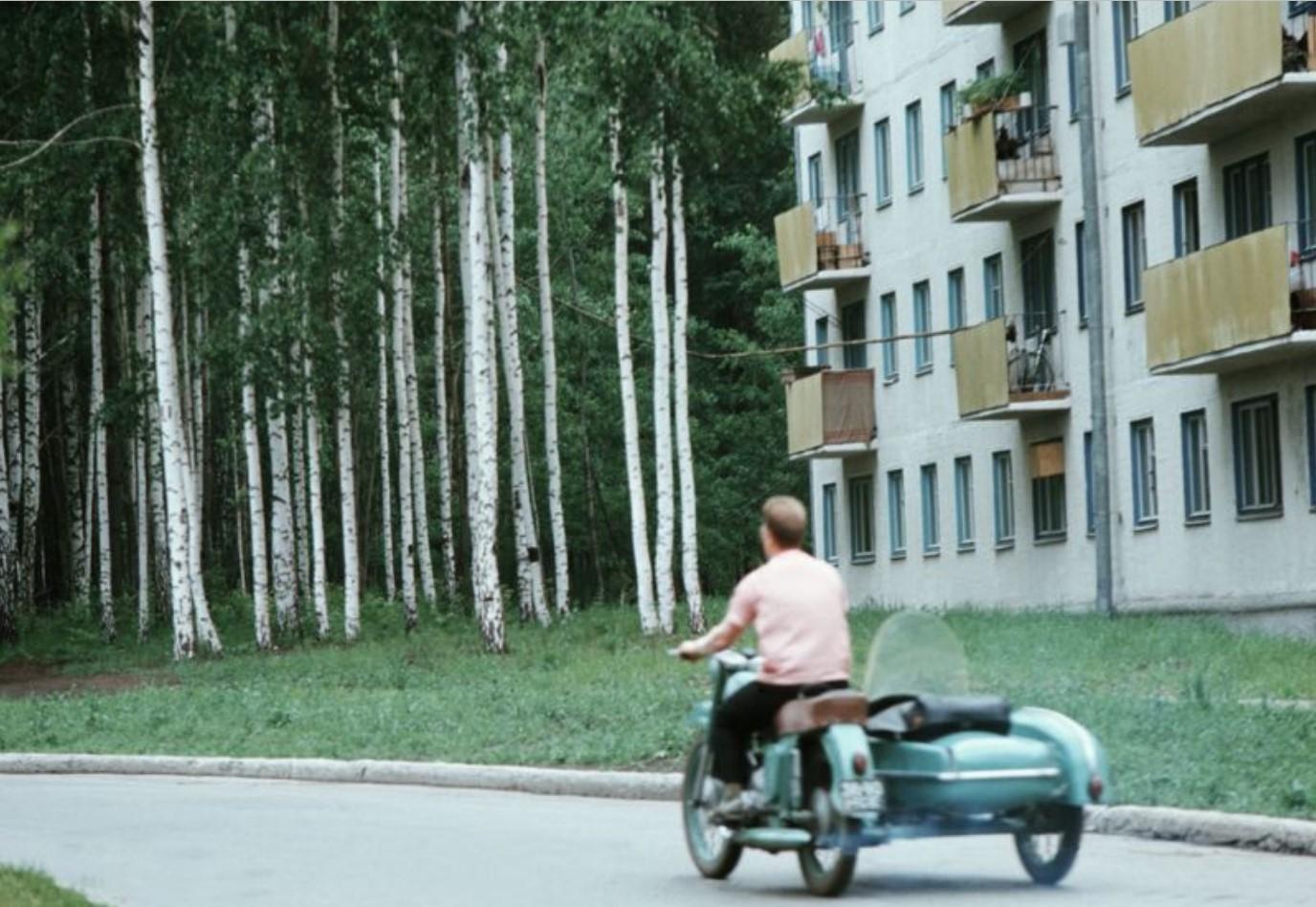 Мужчина на мотоцикле в спальном районе