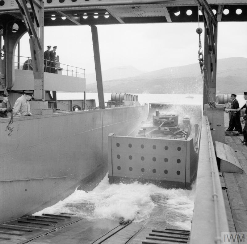 A landing craft containing a Valentine tank being launched down the slipway of a landing ship during combined operations training on Loch Fyne in Scotland, 27 June 1941.