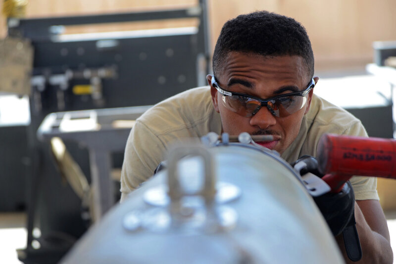 U.S. Air Force Airman 1st Class Tony Chatman, a munitions systems technician currently assigned to the 455th Expeditionary Maintenance Squadron aligns, the front strike of the bomb lugs of a GBU-38. The GBU-38 is the prime bomb utilized with the F-16C Fig