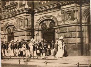 Император Николай II, императрица Александра Фёдоровна, члены императорской фамилии, дворцовый комендант В. А. Дедюлин (во втором ряду свиты, крайний справа у стены собора) и военные чины направляются в храм