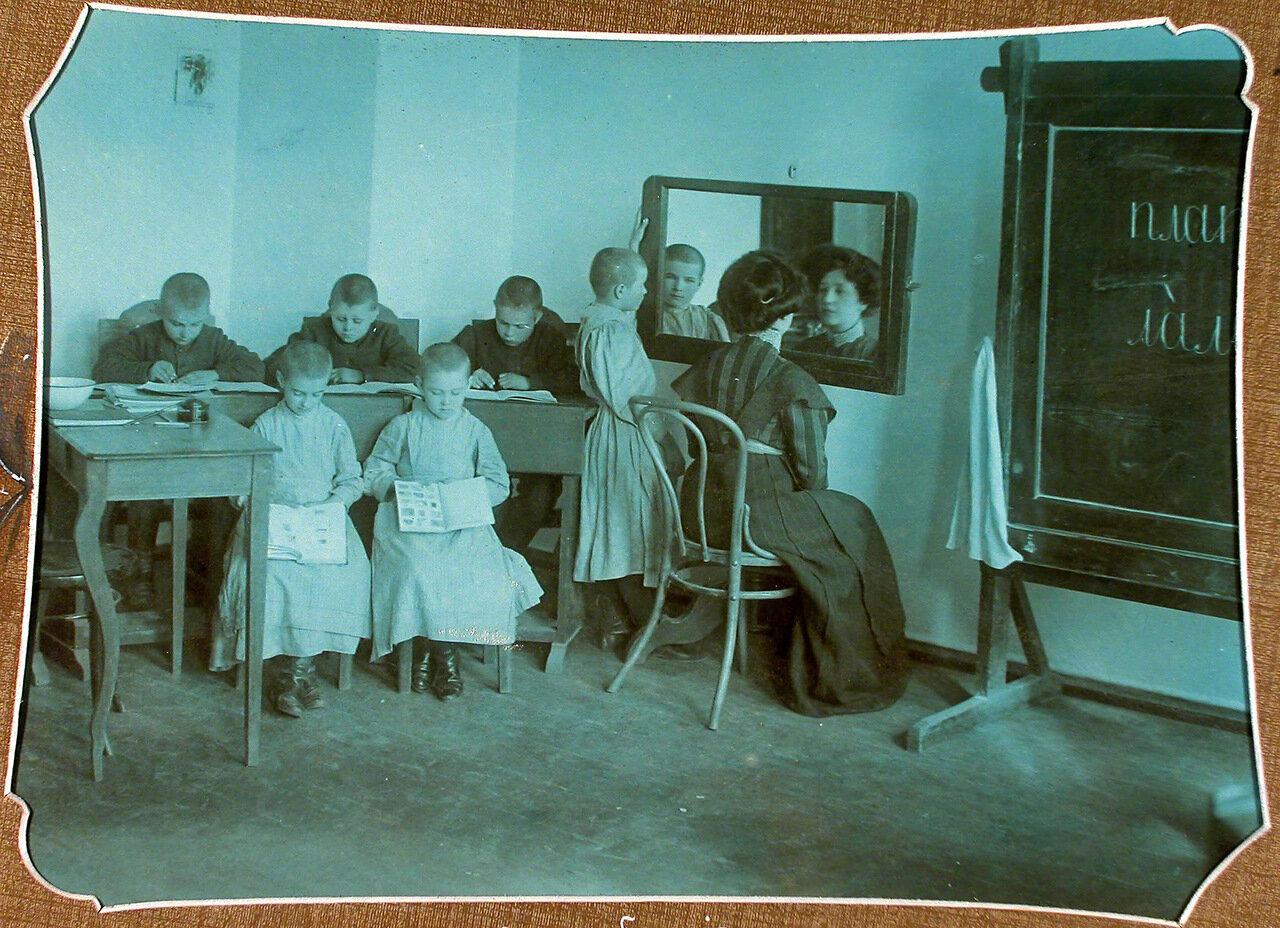 Учительница проводит занятие по артикуляции с учениками 1-го года обучения