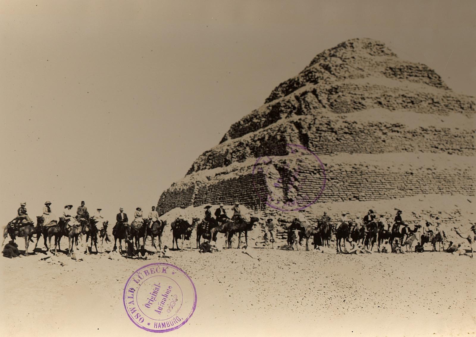Саккара. Туристическая группа на верблюдах и ослах с гидами у подножия ступенчатой пирамиды