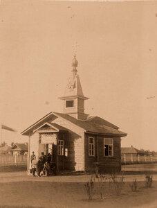 Группа посетителей выставки у модели церкви-школы.