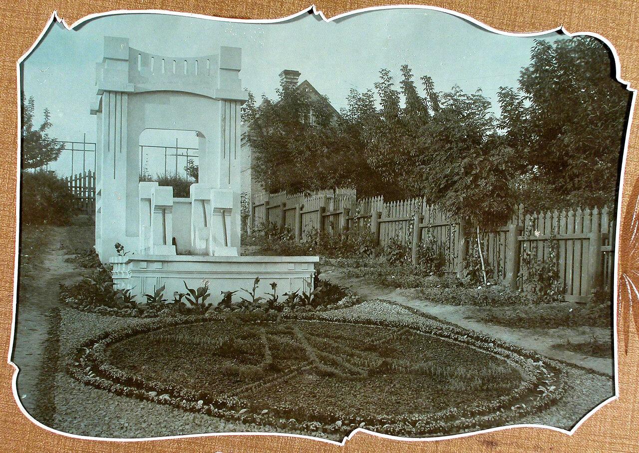 Вид части сада; на первом плане - цветочная клумба и беседка