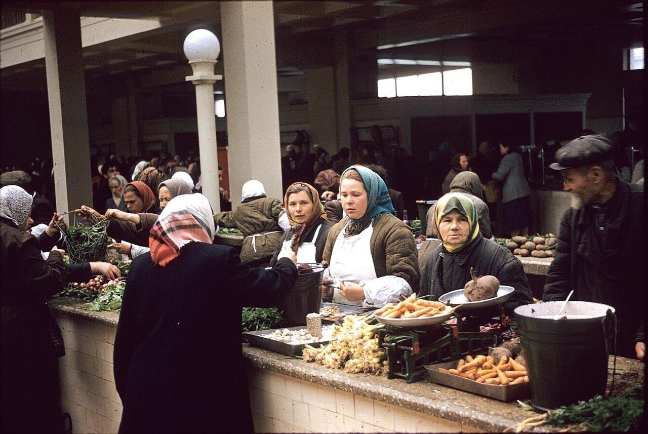 Женщины покупают и продают овощи на рынке